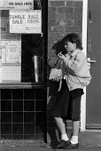 School pupil eating a bag of chips for lunch in the street as the price of a school meal doubles. Bradford - John Harris - 04-11-1988