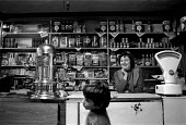 Proprietor and child buying sweets in a local Italian corner shop and cafe, Penrhiwceiber, Cynon valley an area of low family income, poor housing and deprivation. South Wales 1989 - John Harris - 1980s,1989,bought,boy,boys,Bracchi,BUY,buyer,buyers,buying,child,CHILDHOOD,children,commodities,commodity,confectionery,consumer,consumers,Corner Shop,customer,customers,EARNINGS,EBF,ebf economy busin