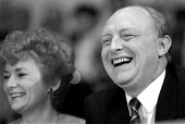 Glenys Kinnock and Neil Kinnock MP laughing at the start of the general election campaign Red Rose Rally Birmingham Town Hall - John Harris - 1980s,1989,Birmingham,funny,Humor,HUMOROUS,HUMOUR,joking,Labour Party,LAUGH,laughing,LAUGHTER,Neil Kinnock,POL politics,rallies,Rally,wellbeing,West Midlands
