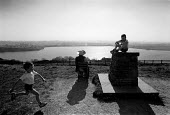 Children playing on a trig point above the Rivington reservoir Lancashire whilst Grandmother enjoys the view during a holiday weekend - John Harris - 1980s,1989,access,adult,adults,amenities,amenity,boy,boys,child,CHILDHOOD,Children,country,countryside,EBF economy business,ENI environmental issues,families,family,female,females,girl,girls,Grandmoth
