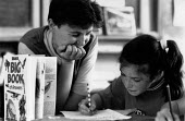 Teacher helping pupil with writing English lesson at a Primary School - John Harris - ,1980s,1989,answering,answers,book,books,child,CHILDHOOD,children,class,communicating,communication,EDU education,female,females,girl,girls,helping,job,jobs,juvenile,juveniles,kid,kids,Knowledge,LAB L