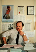 Inland Revenue Tax collector making a telephone call. Many find pin up calendars featuring so called glamour photographs of women sexist and offensive and argue that such material is inappropriate for... - John Harris - 20-02-1990