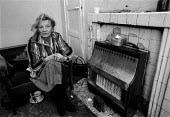 Old age pensioner trying to keep warm during very cold weather. Every winter 30,000 - 60,000 people in the UK die of cold related illnesses - avoidable deaths caused by poor housing and low incomes. P... - John Harris - 18-01-1991