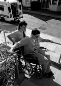Ambulance crew help a disabled out patient in a wheel chair up steps to her home - John Harris - 10-05-1991
