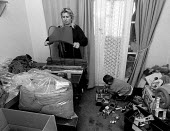 Women homeworker checking and packing tights for low pay whilst her child plays Leicester 14/11/91 - John Harris - 14-11-1991
