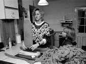 Women homeworker checking and packing tights for low pay whilst her child plays Leicester 1991 - John Harris - 14-11-1991