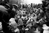Police making arrests. Blockade the base women protest by sitting down at Greenham Common USAF American Airforce Base from which cruse missile launchers were deployed. 1982 - John Harris - 1980s,1982,activist,activists,adult,adults,Air force,Airbase,airbases,Airforce,American,americans,anti war,Antiwar,armed forces,atomic,Blockade,Blockades,Blockading,bomb,BOMBS,Campaign,Campaign for Nu