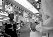 Fast food chain worker serving customer. These workers are typically low paid, McDonalds take away food - John Harris - 09-06-1992