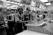 Fast food chain worker serving customer. These workers are typically low paid. McDonald's take-away food - John Harris - 09-06-1992