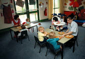 Child eating lunch at a nursery which cares for office workers children - John Harris - 04-06-1993
