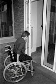 Disabled office worker getting access to her work place. The building has been designed for wheelchair access - John Harris - 09-11-1993