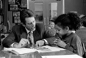 OFSTED - Office For Standards in Education inspector inspecting at a midlands Junior school. Working with a pupil - John Harris - 18-11-1993