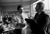 OFSTED - Office For Standards in Education inspector inspecting class teaching at a midlands Junior school. Talking to a teacher - John Harris - 18-11-1993