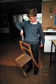 Secondary school pupil using scales to measure the weight of a chair during a physics lesson - John Harris - 09-04-1995