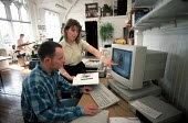 Designer and DTP computer operator working on a page layout in a design studio of a small companydate uncertain - John Harris - 12-12-1996