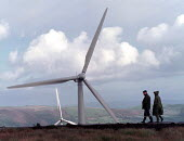 Couple walking Europe's largest wind farm near Carno in Mid Wales. 56 turbines produce enough electricity to serve the average needs of 250,000 homes supplied at half the cost of local domestic power... - John Harris - 27-10-1996