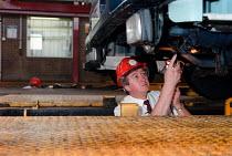 Worker inspecting an HGV, MOT testing at a Heavy Vehicle test centre - John Harris - 1990s,1997,dvla,EBF economy,employee,employees,Employment,eni environmental issues,europeregi,failed,failure,HAULAGE,HAULIER,HAULIERS,Heavy,hgv,hgvs,INSPECTING,inspection,INSPECTOR,INSPECTORS,job,jobs