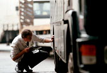 Worker inspecting an HGV, MOT testing at a Heavy Vehicle test centre - John Harris - 1990s,1997,dvla,dvlc,EBF economy,employee,employees,Employment,eni environmental issues,europeregi,failed,failure,HAULAGE,HAULIER,HAULIERS,Heavy,hgv,hgvs,INSPECTING,inspection,INSPECTOR,INSPECTORS,job