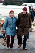 Pensioners shopping at car boot sale - John Harris - 1990s,1997,adult,adults,age,ageing population,boot,bought,buy,buyer,buyers,buying,cold,commodities,commodity,consumer,consumers,couple,COUPLES,customer,customers,EBF,EBF economy,Economic,Economy,elder