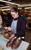 Women worker at Doc Martin boots factory inspecting product quality during the manufacturing process - John Harris - 16-12-1997