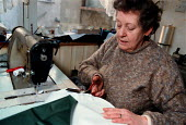Home worker, earning a low wage sewing together flags and pennants Leeds - John Harris - 03-03-1998