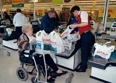Disabled women shopping at a supermarket in the Midlands. The top five largest supermarket chains account for three-quarters of the spending on groceries in the UK. Supermarket are amoungst the lowest... - John Harris - 1990s,1998,assistant,assistants,bought,bound,buy,buyer,buyers,buying,cashier,cashiers,check,checkout,commodities,commodity,consumer,consumers,Customer,Customers,disabilities,disability,disable,disable