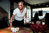 Waitress cleaning up after customers in a cafe restaurant - John Harris - 01-06-1998