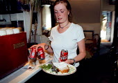Waitress cleaning up after customers in a cafe restaurantShe is a single parent working in a small business serving mainly tourists - John Harris - 01-06-1998