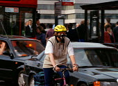 Cyclist with mask as commuters journey home. The air quality is low due to the pollution levels from exhaust fumes. - John Harris - 08-07-1998