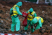 Contractors wearing protective clothing and breathing apparatus removing asbestos from a refuse tip The asbestos was found by workers clearing the site for housing to be built. Nearby residents had be... - John Harris - 03-09-1998