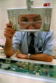 Operator inspecting electronic components mounted on printed circuit boards for communications and computer equipment, during the production process in a modern hi-tech Fujitsu factory - John Harris - 1990s,1998,boards,capitalism,capitalist,chip,chips,COMPUTE,computer,COMPUTERS,COMPUTING,cwu,EBF economy business,ELECTRONIC,electronics,equipment,FACTORIES,factory,Fujitsu,hi,high,Industries,industry,