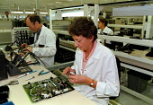 Operator fitting electronic components mounted on printed circuit boards for communications and computer equipment, during the production process in a modern hi-tech Fujitsu factory - John Harris - 1990s,1998,assembly,boards,capitalism,capitalist,chip,chips,COMPUTE,Computer,COMPUTERS,COMPUTING,cwu,EBF economy,ELECTRONIC,electronics,engineer,engineers,equipment,FACTORIES,factory,female,fitting,Fu