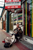 Musician playing a banjo for money in front of a shop for sale Corby - once a thriving steel town. - John Harris - 06-11-1998