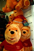 Winnie the Pooh cuddly toys on sale in a toy department of a High Street chain store as Christmas shopping has begun. They are made in China where wages are very low, where children and slave labor is... - John Harris - 30-11-1998