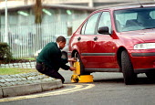 Company security guard fitting a wheel clamp to a car parked on double yellow lines. - John Harris - 02-12-1998