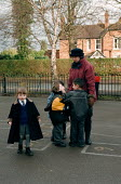 Teacher on playground duty comforting a distressed child and talking to children in playtime in the playground of Shottery Village Junior and infant school. - John Harris - 12-01-1999