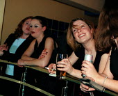 Girls having a drink and discussing the young lads nearby. Saturday night 'Bar M' Stratford on Avon - John Harris - 20-03-1999