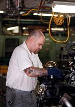 Engineer assembling engine unit on the production line at the Rover Longbridge car plant Birmingham owned by BMW - John Harris - 1990s,1999,assembling,AUTO,auto industry,AUTOMOBILE,AUTOMOBILES,Automotive,Birmingham,BMW,capitalism,capitalist,CAR,Car Industry,carindustry,CARS,cities,city,COMPONENT,components,EBF Economy,engine,En