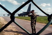USAF soldier looking through binoculars whilst guarding American B52 bombers at the perimeter fence at RAF Fairford air base from which NATO air strikes against Serb targets in Yugoslavia and Kosovo h... - John Harris - 1990s,1999,Aeroplane,AEROPLANES,against,air transport,airbase,AIRCRAFT,airforce,American,americans,armed forces,aviation,Balkan,balkans,BINOCULAR,binoculars,bomber,communicating,communication,conversa