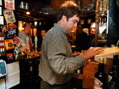 Bar staff using till and serving customers in a Pub - John Harris - 17-03-1999