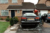 Cleaning the car in the front drive of a house on an estate in Derby - John Harris - 25-04-1999