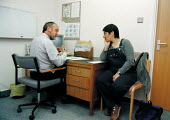Doctor in consultation with pregnant patient at 34 weeks, antenatal clinic in a Hospital - John Harris - 11-05-1999