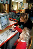 Classroom assistant helping pupils to use a computer Maths lesson at a Primary School - John Harris - 18-10-1999