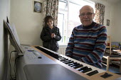 Emilio listening to his grandad play the piano in his sheltered accommodation, Telford. - John Harris - 27-03-2010
