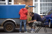 A boy watching his father rewiring the rear lights of a trailer in the street outside his house. Stratford upon Avon Warwickshire. - John Harris - 2010,2010s,adolescence,adolescent,adolescents,AUTO,AUTOMOBILE,AUTOMOBILES,AUTOMOTIVE,boy,boys,car,cars,child,CHILDHOOD,children,communicating,communication,conversation,conversations,DAD,DADDIES,DADDY