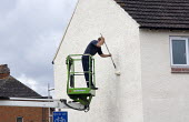 A painter whitewashing the side of a house from a cherrypicker or hydraulic platform - John Harris - 09-09-2011