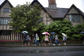 Tourists visiting historic Stratford on Avon in the rain walk past Halls Croft, the mansion was the residence of Shakespeares daughter, Susanna, and her physician husband, John Hall. A Shakespeare Tru... - John Harris - 2010s,2011,asian,asians,chinese,CLIMATE,conditions,daughter,DAUGHTERS,female,females,foreign,foreigner,foreigners,girl,girls,historic,holiday,holiday maker,holiday makers,holidaymaker,holidaymakers,ho