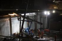 Construction workers demolishing part of a building at night. Birmingham City centre - John Harris - 12-11-2011