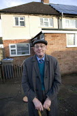 Pensioner outside his Housing Association home where he lives alone, Stratford upon Avon, Warwickshire. - John Harris - ,2010s,2012,adult,adults,age,ageing population,alone,elderly,EQUALITY,excluded,exclusion,flat cap,HARDSHIP,hat,hats,home,house,houses,housing,Housing Estate,impoverished,impoverishment,INEQUALITY,lone