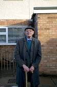 Pensioner outside his Housing Association home where he lives alone, Stratford upon Avon, Warwickshire. - John Harris - 2010s,2012,adult,adults,age,ageing population,alone,elderly,EQUALITY,excluded,exclusion,flat cap,HARDSHIP,hat,hats,home,house,houses,housing,Housing Estate,impoverished,impoverishment,INEQUALITY,lone,